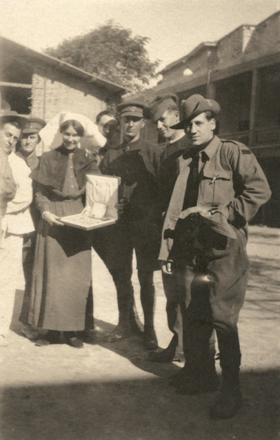 Marjorie surrounded by Australian soldiers as she holds a newly opened Christmas gift.